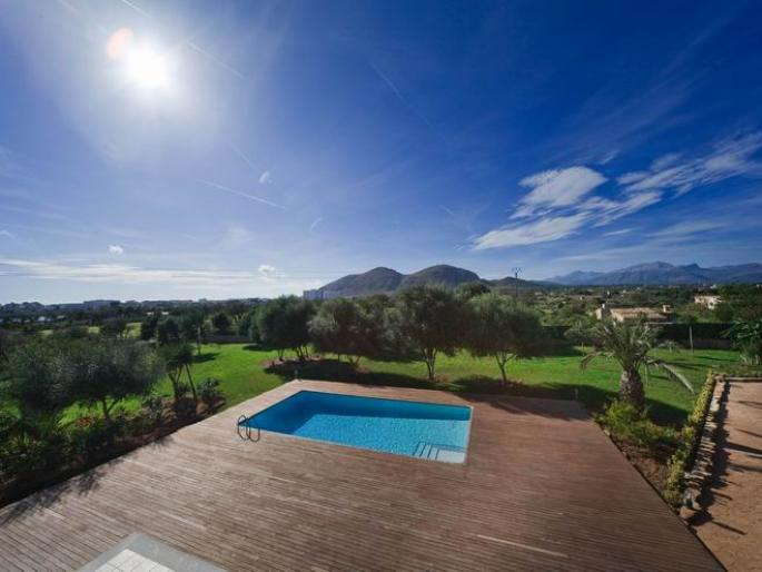 wideangle view at a house with pool and alcudia in the background