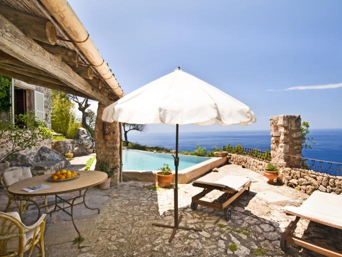 Cozy terrace of a villa in Deià with a table with oranges, a parasol, and an ocean view