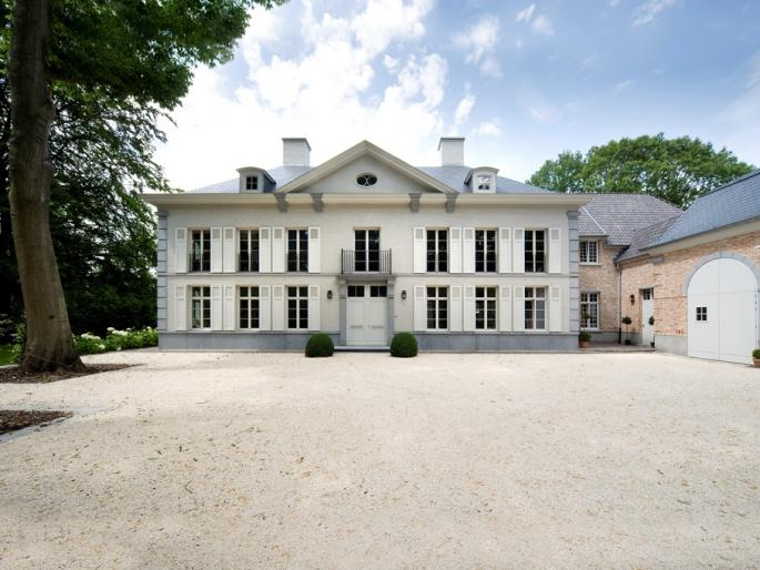 Frontal view of an impressive villa in Brussels with an additional wing for the staff.