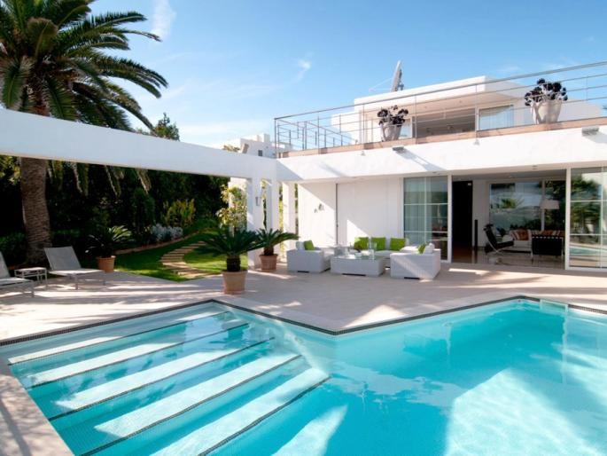 View on a modern villa in Porto Cristo, complete with Pool, a terrace with many sun chairs, and a roof terrace.
