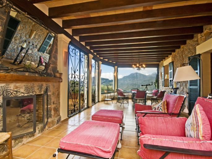 Comfortable living room with red armchairs, a fireplace, and a great view in a villa in Sóller