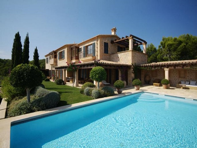 View of a country house made ​​of natural stone in Camp de Mar with a spacious pool and mediterranean plants.