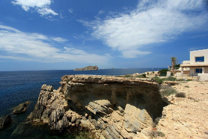 Fantastic view at a stone cliff right next to the sea on Ibiza, connected to a villa