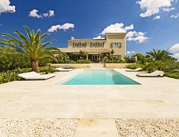 View on a modern finca in Llucmajor with a pool and surrounded by palm trees.