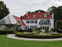View on an impressive villa in Waterloo with a winter garden and well-kept gardens