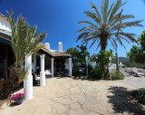 Outside terrace of a Finca on Ibiza, surrounded by palmtrees and bright blue skies