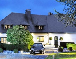 Front view of a luxury property in Eupen, with indirect lighting, a landscaped garden and a car in the driveway