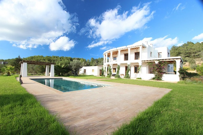 View of a modern villa in Santa Eulalia surrounded by nature with a pool in a minimalist design.