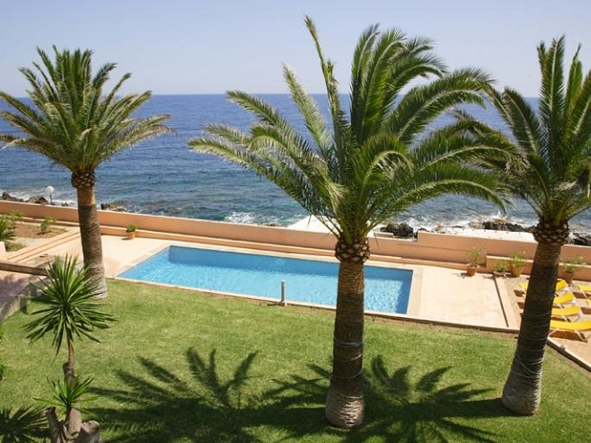 View from a villa in Artà on the landscaped garden with palm trees and a pool