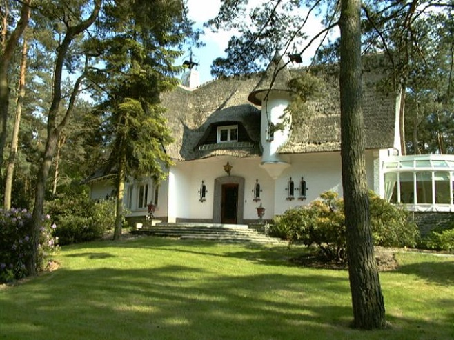 View of a villa with a thatched roof surrounded by a beautiful garden with trees in Keerbergen