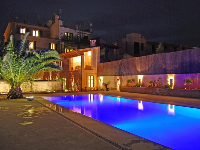 View of a spacious townhouse in Sóller in Mallorcan style with terrace and pool in the twilight
